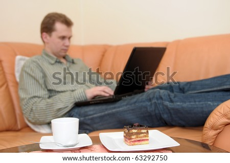 Closeup of the cup of coffee and coffeecake on a table. Young man with portable computer relaxing on sofa in the background. - stock photo