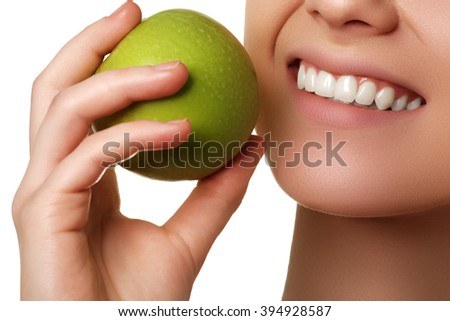 Closeup of the face of a woman eating a green apple, isolated against white background. Beautiful face of young adult woman with clean fresh skin - stock photo