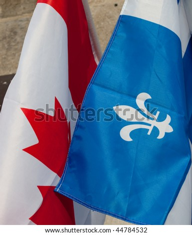Closeup of the flags of Quebec and Canada - stock photo