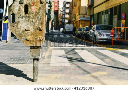 closeup of the hammer of an excavator in the roadworks of a street ready to digging the asphalt - stock photo