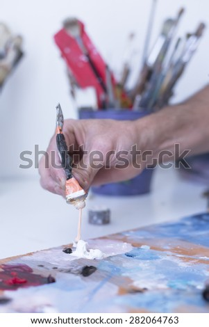 closeup of the hand of a male painter adding paint to the palette at his painting studio - focus on paint - stock photo