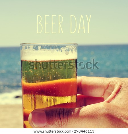 closeup of the hand of a man with a refrehing beer near the sea and the text beer day - stock photo