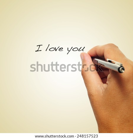closeup of the hand of a man writing with a pen the sentence I love you on a beige background, with a retro effect - stock photo