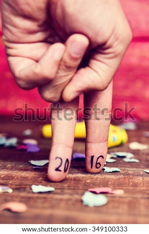 closeup of the hand of a young man doing the action of walking with his fingers, with the number 2016, as the new year, written in them, on a rustic table with confetti and party horns - stock photo