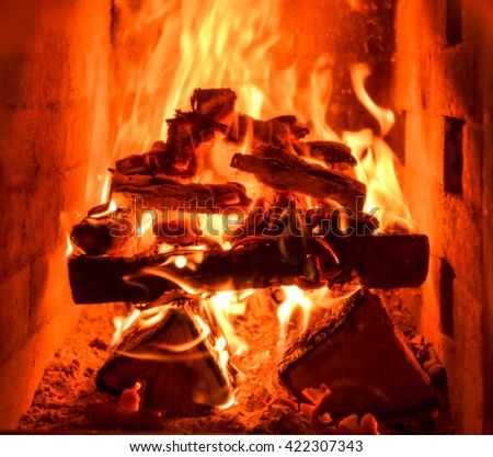 Closeup of the inside of home traditional fireplace running on natural hard wood with flames and heat. - stock photo