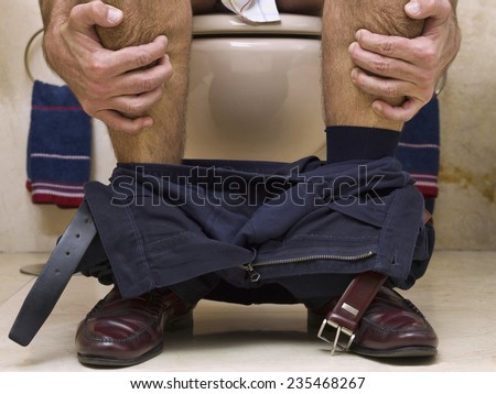 Closeup of the legs of a man sitting on the toilet, holding hands. - stock photo