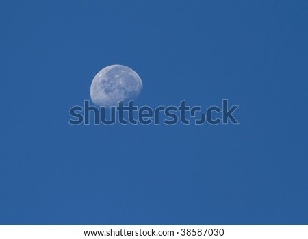 closeup of the moon during the day in a blue sky - stock photo