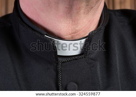 Closeup of the neck of a priest wearing a black shirt with cassock and white clerical collar - stock photo