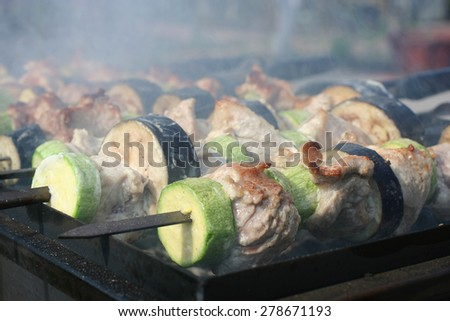Closeup of the pork with zucchini and eggplant roasted on skewers - stock photo