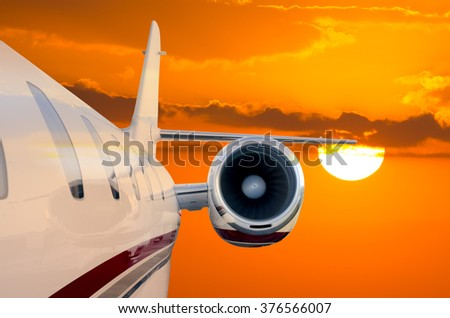 Closeup of the side of a private jet airplane flying soaring through the air with a beautiful orange sunset in the background and reflecting off of the plane - stock photo