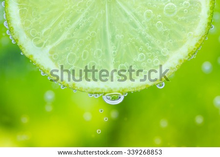 Closeup of the texture of sliced lime in the water with bubbles - stock photo