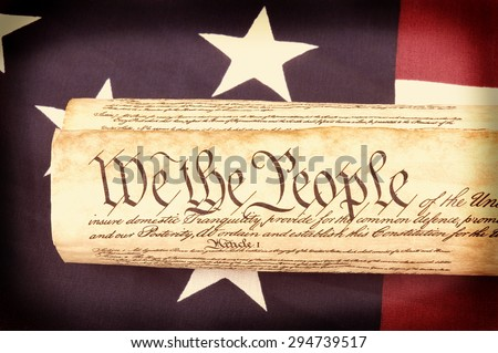Closeup of the United States Constitution on an American flag with retro filter and vignette applied. Perfect for USA patriotic holiday projects. - stock photo
