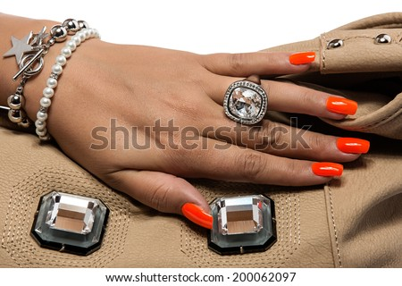 closeup of the woman's hand wearing luxury ring, orange nail art manicure with mirror leather bag. wearing large silver ring, isolated on white studio background - stock photo