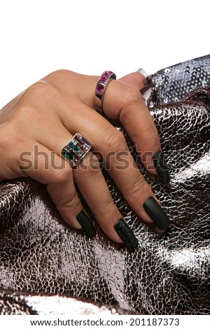 closeup of the woman'??s hand wearing luxury rings, black nail art manicure on silver sequin material background  - stock photo