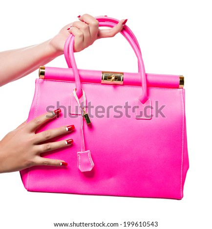 closeup of the woman's hand with red art manicure, holding pink neon handbag isolated on white studio background - stock photo