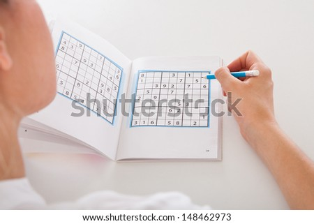 Closeup Of The Young Woman Solving Sudoku - stock photo