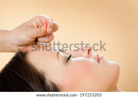 Closeup of therapist giving acupuncture treatment to female customer in beauty spa - stock photo
