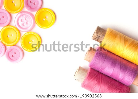 Closeup of thread and collection of various sewing buttons. Isolated on white - stock photo