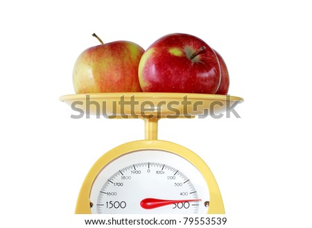 Closeup of three apples lying on weight scale. Isolated on white with clipping path - stock photo