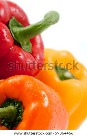 closeup of three bell peppers on white, focus on orange pepper - stock photo