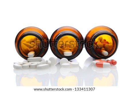 Closeup of three brown prescription bottles on their sides with pills spilling onto white reflective surface. Shallow depth of field with focus on foreground medicine. - stock photo
