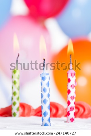 Closeup of three burning birthday candles on top of a cake - stock photo
