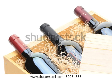 Closeup of three Cabernet Sauvignon wine bottles on their side in a wooden crate. Crate lid is pulled partially back exposing the bottles and packing excelsior. Horizontal format isolated on white. - stock photo