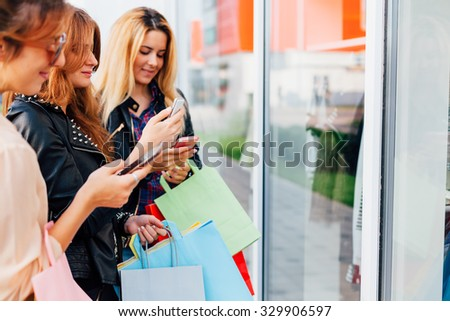 Closeup of three girls using mobile phones with shopping bags - stock photo