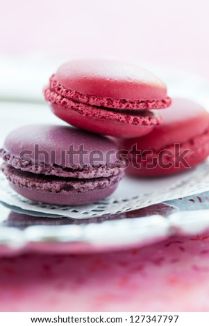Closeup of three sweet macaroons on white decorative mat - stock photo
