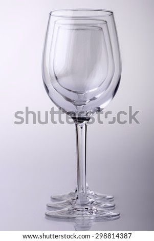 Closeup of three transparent clear crystal empty wine glasses standing close to each other in row isolated on chromium white and grey background, vertical picture - stock photo