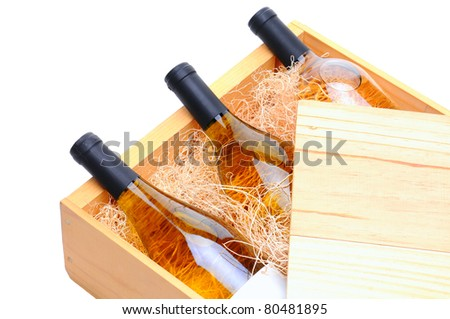 Closeup of three white wine bottles on their side in a wooden crate. Crate lid is pulled partially back exposing the bottles and packing excelsior. Horizontal format isolated on white. - stock photo