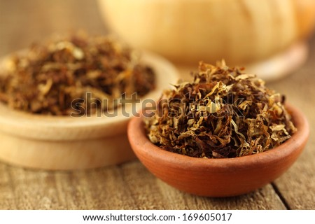 Closeup of tobacco for making cigarette on brown bowl - stock photo