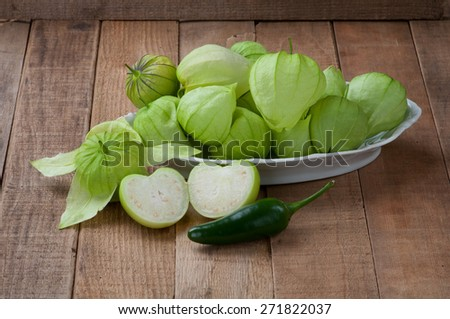 Closeup of Tomatillos (Mexican Husk Tomato)  in a Bowl with Jalapeno Pepper on rustic board table background.  Used in Verde Sauce, Salsa, enchiladas, pork chile, soup.  Horizontal side light view - stock photo