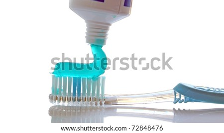 closeup of toothpaste coming out of a tube on white - stock photo