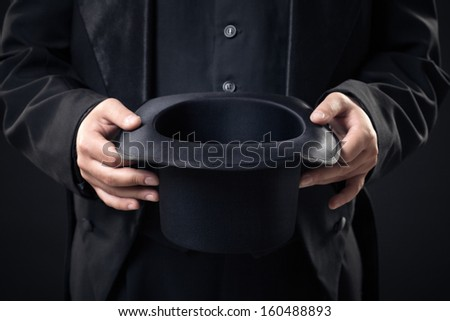 closeup of top hat in magician hands isolated on dark background - stock photo