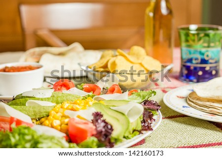 Closeup of traditional mexican food in a table, with a plate of fresh salad, tortillas, chicken fajitas, nachos and a bowl of spicy sauce - stock photo