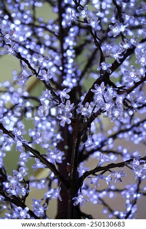 Closeup of tree branches with blue twinkle lights - stock photo