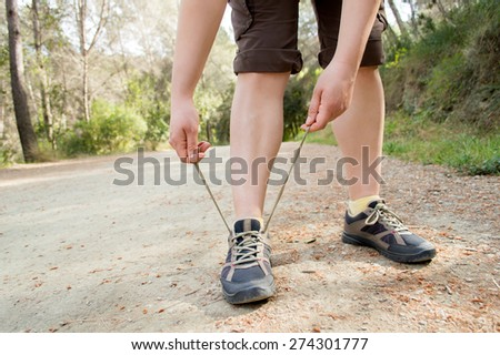 closeup of trekking boots being tied by woman getting ready for trekking  - stock photo