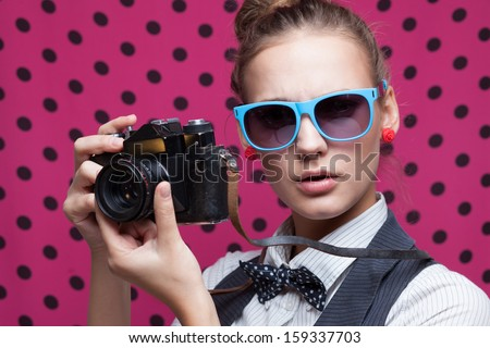 Closeup of trendy girl face in colorful sunglasses with vintage camera - stock photo