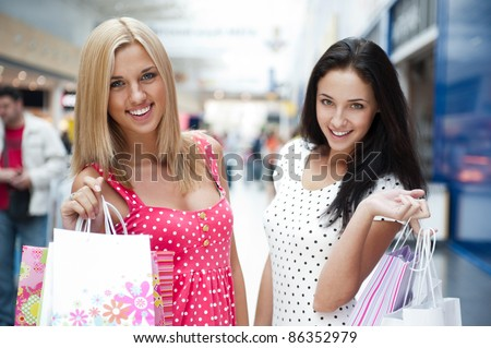Closeup of two attractive happy girls out shopping - stock photo