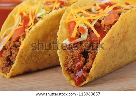 Closeup of two beef tacos with tomato, cheese, lettuce and sauce - stock photo