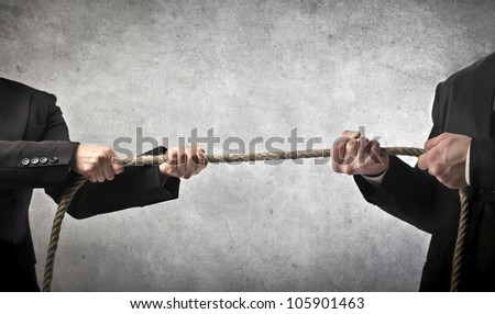 Closeup of two businessmen playing tug of war - stock photo
