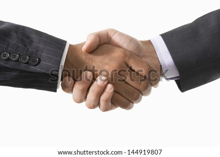Closeup of two businessmen shaking hands against white background - stock photo