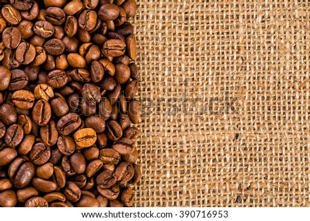 Closeup of two coffee beans at roasted coffee heap. Coffee bean on macro ground coffee background. Arabic roasting coffee - ingredient of hot beverage. - stock photo