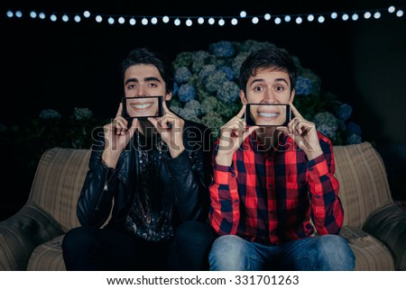 Closeup of two funny young men holding smartphones over their faces showing female mouths smiling in the screen on a outdoors party. Friendship and celebrations concept. - stock photo