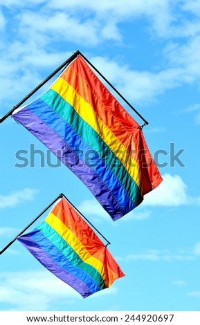 Closeup Of Two Gay Pride Rainbow Flags Against Blue Sky With White Clouds. - stock photo