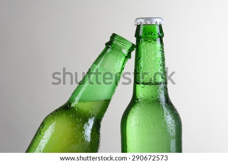 Closeup of two green beer bottles against a light to dark gray background. One bottle is at a slant leaning on the other bottle. Horizontal format with copy space. - stock photo