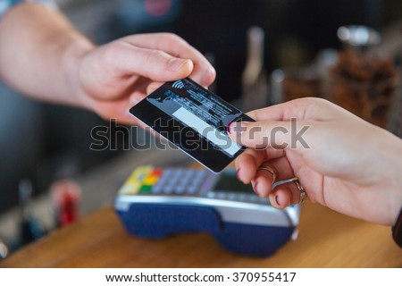 Closeup of two hands holding credit card for paying with reader - stock photo