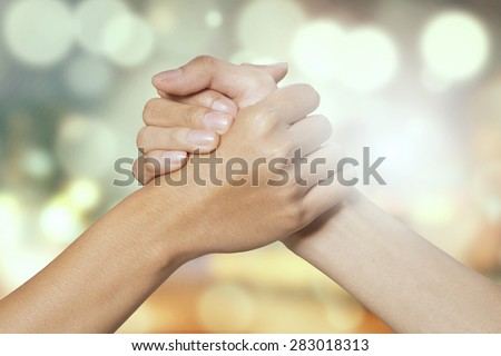 Closeup of two hands joining together, symbolizing to trust each other, shot with a bokeh background - stock photo