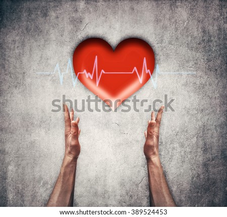 Closeup of two human hands holding a red heart with ecg line. Health care, medicine and charity concept - stock photo